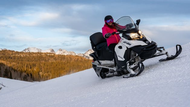 a woman riding a snowmobile down a snow covered slope