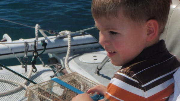 a little boy sitting on a boat