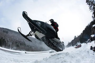 a man flying through the air while riding a snow board