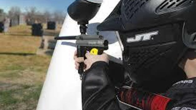 man aiming paintball gun behind obstacle