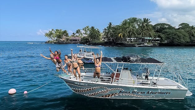 group of people jumping off a boat into the water