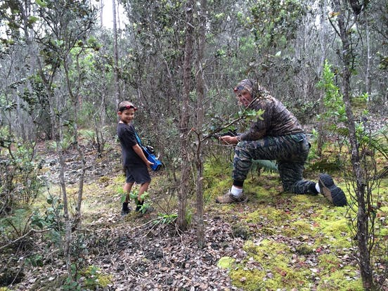 A small boy and a man hiding in the forest with laser tag guns in Hawaii