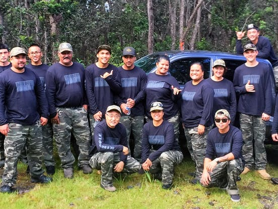 Team auto body with black shirts and camouflage pants in front of a truck in a cloud forest in Hawaii