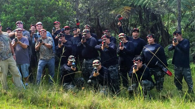 A group of people decked out in camouflage and black holding up laser tag guns in a cloud forest in Hawaii