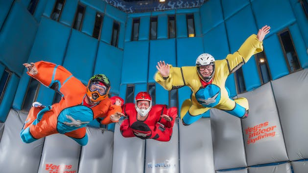 three people in orange, red and yellow at vegas indoor skydiving