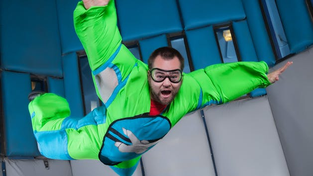 a man in a green suit inside a wind tunnel