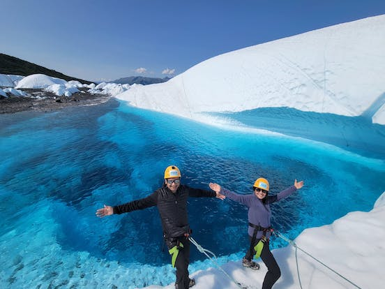 A Man and a Woman tethered in front a blue pool on a glacier