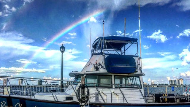 deep obsession boat with rainbow in the background