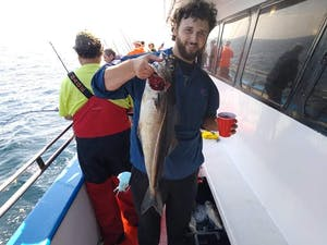 a person holding a fish on a boat posing for the camera