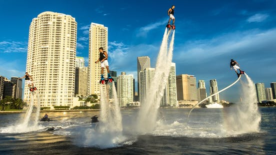 4 People Flyboarding Against Miami City Background