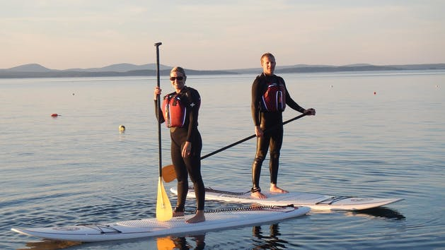 a man and woman stand up paddle boarding on lake