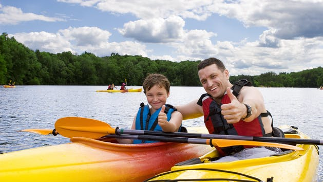 dad and son giving thumbs up in kayaks