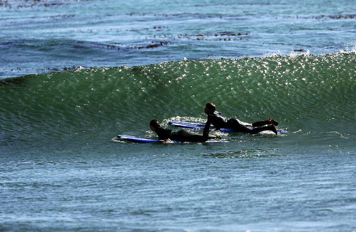 Surfers paddling out