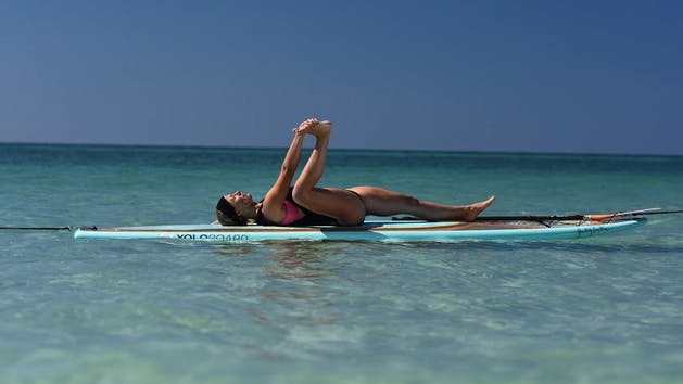A woman stretching and doing FloYo on a SUP