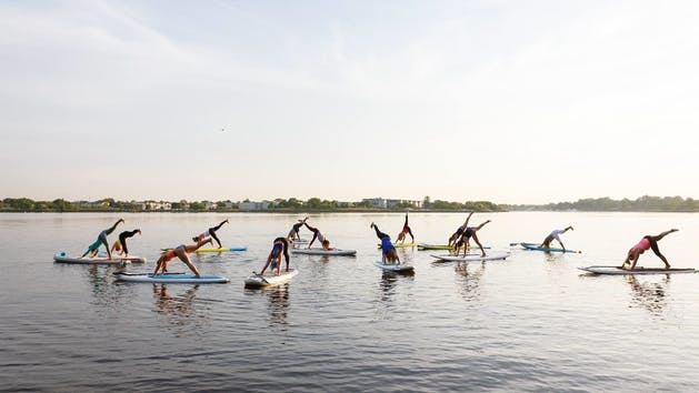 A group of people taking a FloYo class on open water